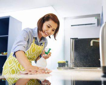 Cheerful pretty young Asian housewife cleaning kitchen counter with desinfecting spray