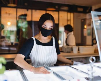 Portrait of young woman with face mask working indoors in cafe, disinfecting surfaces.